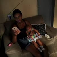 Vanessa, 32, types a text message on her mobile phone as she holds her daughter, Valentina, who is 5-months-old and was born with microcephaly, inside of their house in Jaboatao, near Recife, Brazil, Friday. | REUTERS