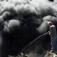 A man tries to extinguish a fire at an illegal garbage dump after residents decided to set fire to it to prevent the spread of the mosquito-borne Zika virus, in a slum of San Jose on Monday. | REUTERS