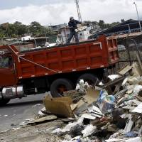 A worker collects garbage during a government campaign to help control the spread of the mosquito-borne Zika virus in the neighborhood of Purral near San Jose, Costa Rica, Thursday. | REUTERS