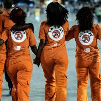 City cleaning workers are seen with the legend 'Out Zika' in Portuguese on their uniforms between the samba schools' during the second night of the carnival parade at Sambadrome in Rio de Janeiro on Tuesday. | AFP-JIJI