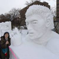Two women pose for a photograph beside a snow sculpture of Ayumu Goromaru, one of the 2015 Rugby World Cup's star players, at the Sapporo Snow Festival on Feb. 5. | KYODO