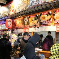 People inspect food stalls at Sapporo Snow Festival on Feb. 5. | KYODO