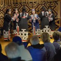 Women wearing traditional Ainu clothes sing and dance before tourists at the Ainu Museum in the town of Shiraoi in Hokkaido on Oct. 24. | KYODO