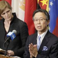 Japanese Ambassador to the United Nations Motohide Yoshikawa speaks to the media as U.S. Ambassador Samantha Power listens following an emergency meeting of the Security Council on Sunday after North Korea launched a rocket. | AP