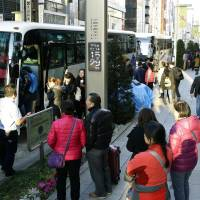 Buses for Chinese tourists park in one of the streets in Tokyo's glitzy Ginza shopping district last month. | KYODO