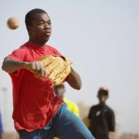 A player tries out for a Japanese project to cultivate professional baseball talent from West Africa in January in an unspecified location. | COURTESY OF ASSOCIATION DES AMIS DU BASEBALL AU BURKINA FASO / KYODO