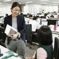 Chihiro Nishijima (left), an employee of Sony Life Insurance Co., talks with her superior at their office in Tokyo's Minato Ward on Jan. 6. | KYODO