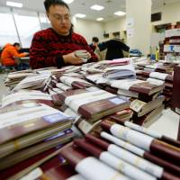 A travel agent handles stacks of clients' passports at the Japanese Embassy in Beijing on Jan. 29, ahead of the Lunar New Year holiday. | KYODO