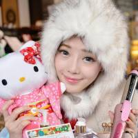 Zhang Yingxi, 21, poses for a photo in Beijing on Jan. 28 with goods she bought in Japan. | KYODO