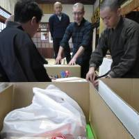 Monks pack snacks given as offerings at Kuonji Temple in Nagoya on Feb. 2 to deliver to impoverished children.   CHUNICHI SHIMBUN