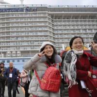 Chinese and other tourists disembark from a cruise ship Feb. 17 at the port of Hakata in Fukuoka Prefecture. | KYODO