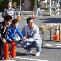 Satoshi Hagiwara (right), a Japanese-Brazilian, participates Nov. 1 with his family members in the first disaster drill for foreign residents held by the city of Takahama, Aichi Prefecture. | KYODO