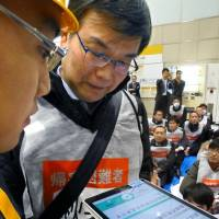 Participants use a translation app on a tablet computer during an earthquake drill in Tokyo on Monday. | KYODO