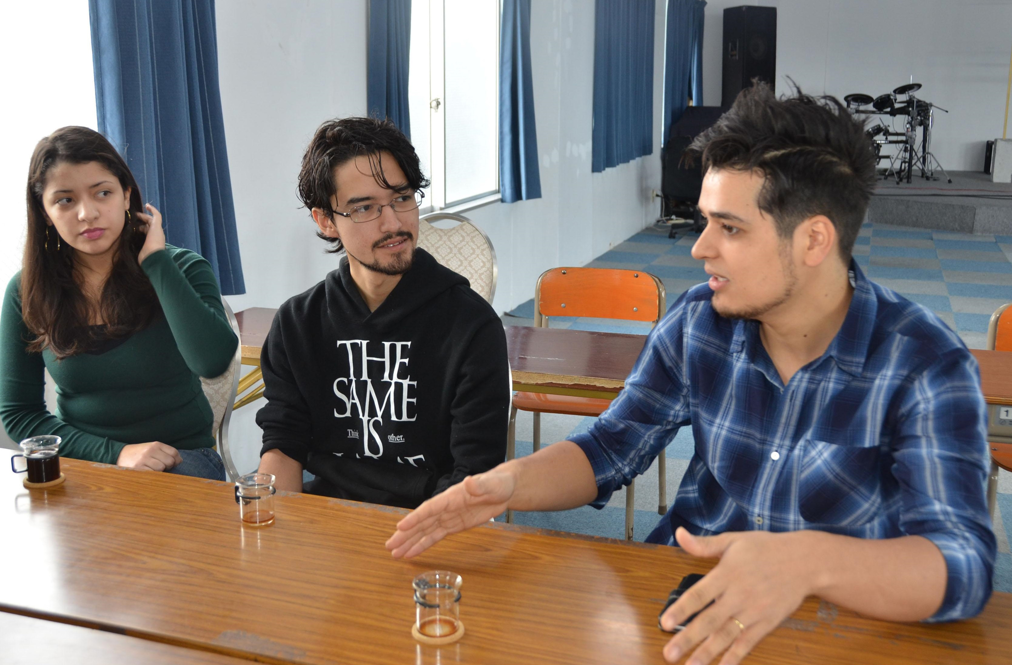 Japanese-Brazilians Silas Alves Okada (right) and Lucas Toshio Suzuchi (center), talk about their teenage experiences of being left out of school while Suzuchi's wife looks on in November in Kamisato, Saitama Prefecture.   KYODO