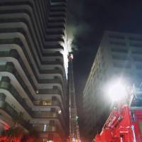 Firefighters work to put out a fire at Forus Tower Tokorozawa, a high-rise condo in Saitama Prefecture, on Monday night. | KYODO