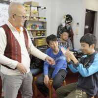 Hiroshi Kohata, who heads the free school Japan Freinet, conducts a science experiment with Koichiro Yazawa (right) and other students on Dec. 3 at the school in Tokyo's Toshima Ward. | KYODO