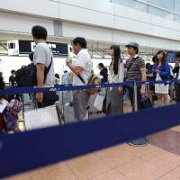 Passengers wait in line at an All Nippon Airways check-in counter at Haneda airport in Tokyo in August 2015. | BLOOMBERG