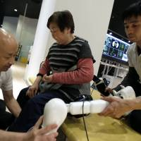 Therapists remove a Cyberdyne Inc. Hybrid Assistive Limb robotic suit from a patient who has paralysis on her left side, at the company's facility in Tsukuba, Ibaraki Prefecture, in January 2014. | BLOOMBERG
