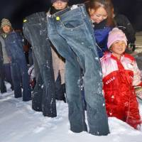 Participants put frozen jeans in the snow in Sarabetsu, Hokkaido, on Sunday. The tongue-in-cheek event was a bid for a Guinness World Record. | KYODO