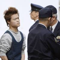 Kazuaki Isono, 21, leaves the Kakogawa police station in Hyogo Prefecture a day after his Thursday arrest on suspicion of beating a 20-year-old woman to death with a hammer. | KYODO