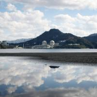 Clouds are reflected in a bay as the buildings housing the Nos. 3 and 4 reactors at Kansai Electric Power Co.'s Takahama nuclear power station loom in the background. | BLOOMBERG