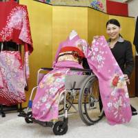 Akiko Nakajima, head of Hanayome Kobo in Kasugai, Aichi Prefecture, shows a kimono that can be put on without standing up. | KYODO