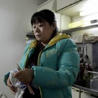 Chinese trainee Tang Xili wipes her chopsticks in a building housing a local labor union office and a shelter for Chinese trainees managed in Hashima, Gifu Prefecture, on Jan. 14. | BLOOMBERG