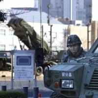 A member of the Self-Defense Forces stands near a Patriot anti-missile unit on Feb. 7 at the Defense Ministry in Tokyo. The unit was deployed ahead of North Korea's recent rocket launch. | AP