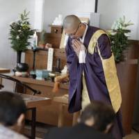 Buddhist monk Kaichi Watanabe addresses a bereaved family at a funeral hall in Yachiyo, Chiba Prefecture, on Jan. 24. | AP