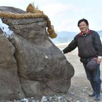 Nobuharu Kanchi stands next to a rock that looks similar to the profile of a monkey, on Kojima Island in December. | KYODO