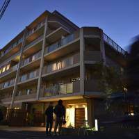 Members of the media stand Tuesday evening outside S Amiyu Kawasaki Saiwai-cho, an elderly care facility in Kawasaki where three residents were fatally thrown from verandas by an ex-worker. | KYODO