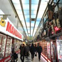 Visitors browse specialty shops selling pop subculture items at Nakano Broadway. | YOSHIAKI MIURA