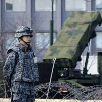 A Self-Defense Force member stands by a PAC-3 Patriot missile unit deployed at the Defense Ministry in Tokyo on Sunday ahead of an anticipated North Korean rocket launch. | AP