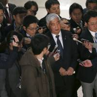 Defense chief Gen Nakatani is questioned by reporters upon arrival at the Defense Ministry in Tokyo on Sunday. | REUTERS