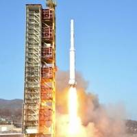 A TV grab from Korean Central Television shows a North Korean rocket lift off from its launchpad in Dongchang-ri Sunday morning. | AFP-JIJI
