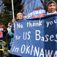 People hold up banners at a rally in front of the Diet on Sunday as they listen to a protester speak out against the long-delayed project to move Futenma air base elsewhere in Okinawa. | AFP-JIJI