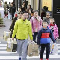 Chinese tourists carry items they purchased in the Ginza shopping district in Tokyo on Sunday during the Lunar New Year holiday. | KYODO
