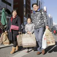 Chinese tourists carry their purchases through Tokyo's Ginza shopping district on Feb. 7, the first day of the seven-day Lunar New Year holiday. | KYODO