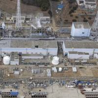 This photograph, taken with a drone-mounted camera in March 2011, shows (from left) Fukushima No. 1 nuclear power plant's reactor No. 4, No. 3, No. 2 and No. 1. | AIR PHOTO SERVICE/KYODO