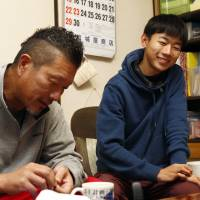 Gaishi Itakura, who lost his mother in the March 2011 disaster, chats with his father at their home in Ishinomaki, Miyagi Prefecture, in November. | KYODO