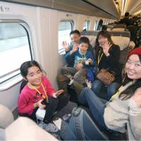 People pose for a photo aboard a bullet train on the Hokkaido Shinkansen Line on Saturday. | POOL/KYODO