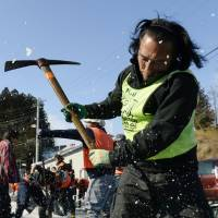Tomohiro Narita, leader of the volunteer group Support the Underground, removes snow and ice on Jan. 31 from a road adjacent to temporary housing where people who lost their homes in the March 2011 killer tsunami now reside in Ichinoseki, Iwate Prefecture.   KYODO