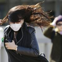 Pedestrians brave strong winds on Sunday in Minato Ward, Tokyo. | KYODO