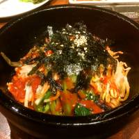 Most evenings, the majority of the seats along the counter are likely to be occupied by solo diners, many of them women picking delicately at their bibimbap rice (above) or chilled reimen noodles. | ROBBIE SWINNERTON