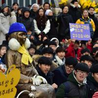 "South Korean students sit near a statue of a teenage girl symbolizing former ""comfort women"" during the weekly demonstration in front of the Japanese Embassy in Seoul on Wednesday. 