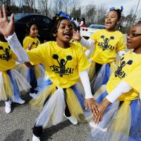 Members of a school cheer team practice dance moves before marching in the North Carolina MLK Black History Month Parade on Feb. 6 in Durham, North Carolina. | AP