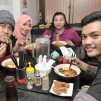 Endy Harmoko (left), a student at Yokohama National University, enjoys a bowl of ramen with his family from Indonesia 
