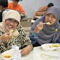 Happy together: Indonesian women eat halal lunches at a Tokyo university in June 2013. | KYODO