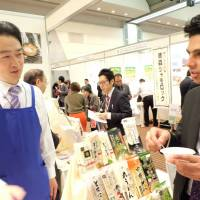 A vendor talks to a visitor at the Japan Halal Expo in Chiba's Makuhari Messe in November. | COURTESY OF HALAL MEDIA JAPAN