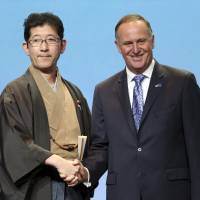 State Minister of Cabinet Office Shuichi Takatori and New Zealand Prime Minister John Key shake hands after signing the Trans-Pacific Partnership Agreement in Auckland on Thursday. | AP